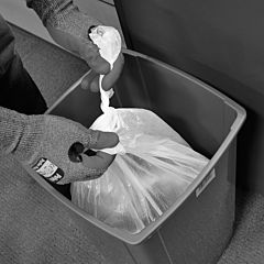 Black and white image of a person tying a white bin bag.