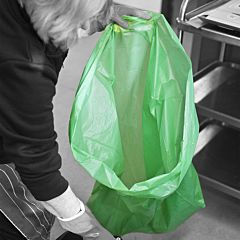 A person holding a green refuse sack.