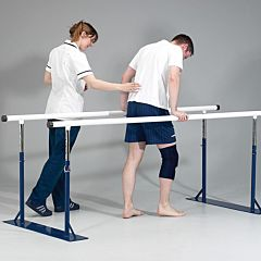 Assistant helping a man with an injured knee using the remedial parallel bars, the base of the bars are dark blue, with silver adjustable inserts and white handrail.